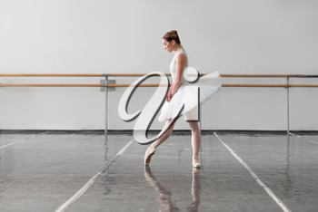 Beautiful female ballet dancer in ballet class, barre and white wall on background