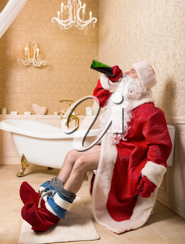 Drunk Santa Claus with bottle of alcohol sitting on the toilet. Christmas humor