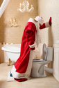 Funny drunk Santa Claus in red costume peeing in the toilet. Father Christmas alcoholic