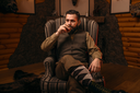 Hunter man in traditional vintage hunting clothing drink luxury alcohol after successful hunt. Fireplace, stuffed wild animals, bear skin and other trophies on background
