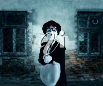 Pantomime actor in glasses shows boxer. Mime in suit, gloves and hat. April fools day concept