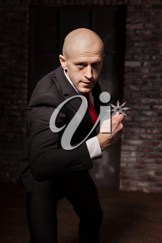 Bald contract killer in suit and red tie holds asterisk ninja. Professional secret agent explore oriental martial arts concept