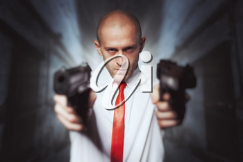 Bald killer in red tie aims with two pistols. Professional secret agent concept. Assassin with guns, wallpaper, background or poster