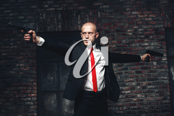 Serious hired assasin in red tie aims with two pistols. Professional secret agent concept. Murderer with guns, wallpaper, background or poster