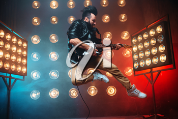 Male performer with electro guitar in a jump on the stage with the decorations of lights. Music entertainment. Bearded musican song performing