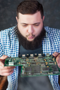 Male computer engineer blows off the dust from motherboard. Electronic devices repairing technology and service support