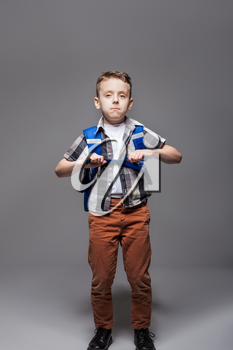 Little schoolboy with schoolbag, studio photo shoot. Young pupil in with backpack. Boy with school bag