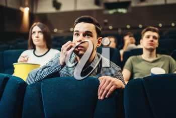 Scared man watching movie in cinema. Showtime, entertainment