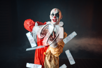 Scary bloody clown with crazy eyes holds fan of money. Man with makeup in carnival costume, mad maniac