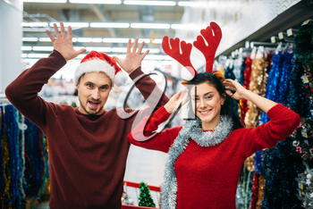 Playful couple choosing christmas decorations in supermarket, family tradition. December shopping of holiday goods