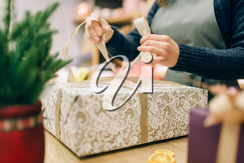 Female person ties a gold bow on gift box, handmade wrapping and decoration process. Woman wraps present on the table, decor procedure