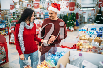 Young couple chooses christmas tree toys in shop, family tradition. December shopping of holiday goods and decorations