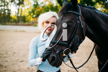 Portrait of woman and horse, horseback riding. Equestrian sport, young woman and beautiful stallion, farm animal