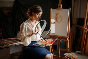 Female painter holds color palette and brush in studio. Creative paintbrush art, artist drawing in class, workshop interior on background