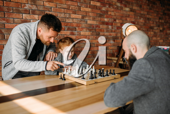 Clever schoolgirl playing chess with man. Young girl at the chessboard, female kid plays logic game