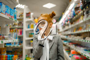 Little school girl looks through magnifying glass, shopping in stationery store