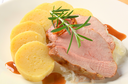 Dish of pork meat with potato dumplings and white cabbage