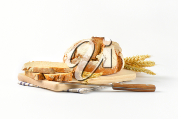 fresh bread - whole cob and slices - on wooden cutting board