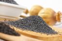 heap of whole poppy seeds on wooden cutting board