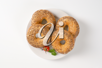 fresh bagels topped with seeds on white plate