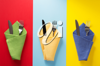 knife and fork at napkin at colorful background