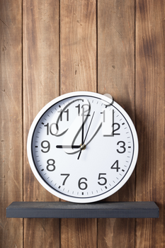 wall clock at shelf on wooden background texture
