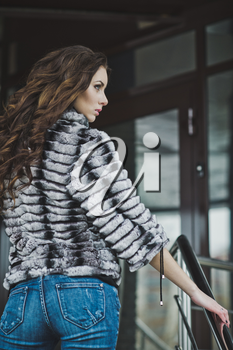 Girl in a fur coat and jeans in the winter on the street.
