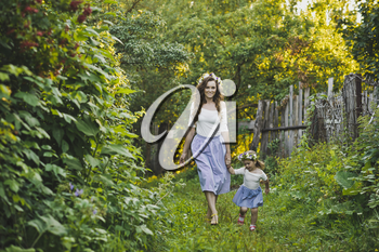 Mother with her little daughter walking in the garden.