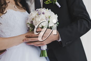 A bouquet of flowers in the hands of the bride.