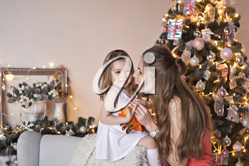 Portrait of the daughter with mother near Christmas tree.