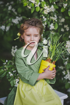 The child holds a tub of sprouted leek.