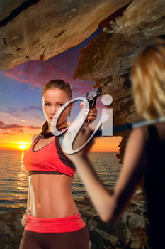 Girl with a pistol in a cave by the sea at sunset is protected from girl with a bat. in search of adventure