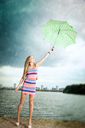 happy girl under an umbrella walks in the rain during the summer along the river against the background of the city