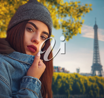 girl against the backdrop of the eiffel tower in Paris in the fall.