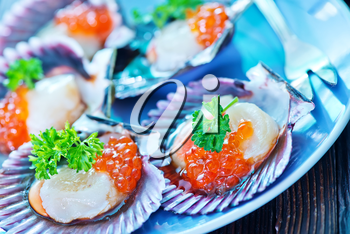 scallop with red caviar on the plate