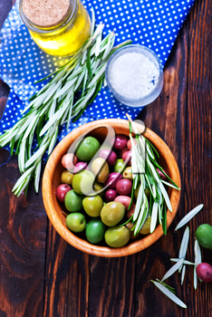green olives in bowl and on a table