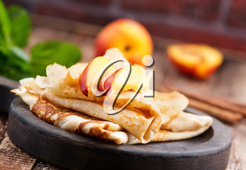 pancake with peach and cinnamon on the wooden board