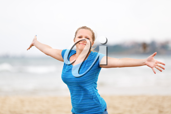 Beautiful young woman enjoying freedom. Free happy girl posing arms outstretched to the side and looking at the camera.