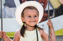Little girl in a hat smiling. Shallow depth of field.