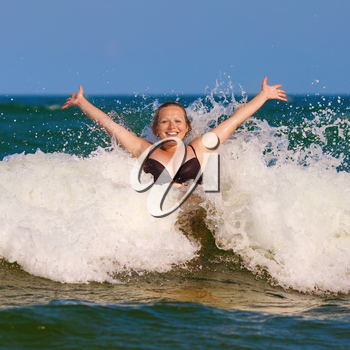 Beautiful smiling girl with her hands raised in the foam of a sea wave. Happy young woman. Bright sunny day.