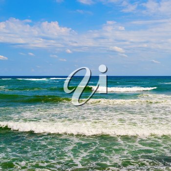 Cloudy blue sky and turquoise surface of the sea with waves.