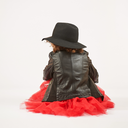 Little girl with black hat sitting and pouting. Back view