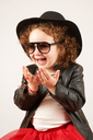 Little girl with black hat and Sunglasses sitting and laughing