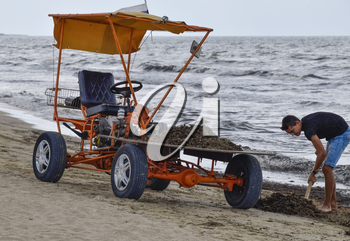 The car for garbage collection from the beach. Cleaning on the beach, clean beach from mud and waste.
