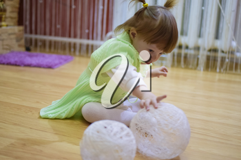 One year old baby girl sitting on the floor. A child playing with wicker balls. A blonde girl.