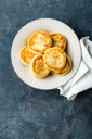 Frying homemade cottage cheese pancakes, syrniki on white plate