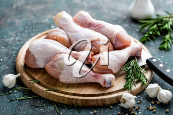 Raw uncooked chicken legs, drumsticks on wooden board, meat with ingredients for cooking