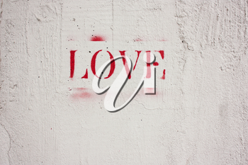 The word love written in red letters on a white wall