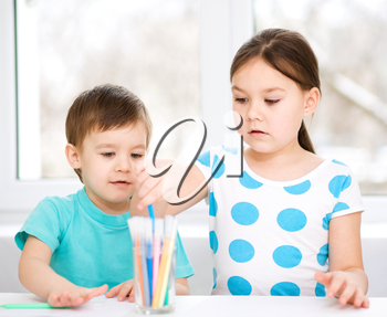 Little children is drawing on white paper using color pencils