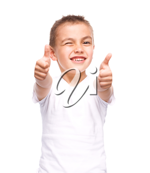 Happy boy is showing thumb up gesture using both hands, isolated over white